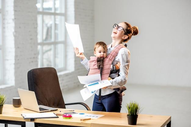 Multitasking zakenvrouw met een stapel papieren documenten met haar zoontje op kantoor