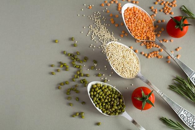 Mung, quinoa en linzen in de lepels op de grijze achtergrond. bovenaanzicht.