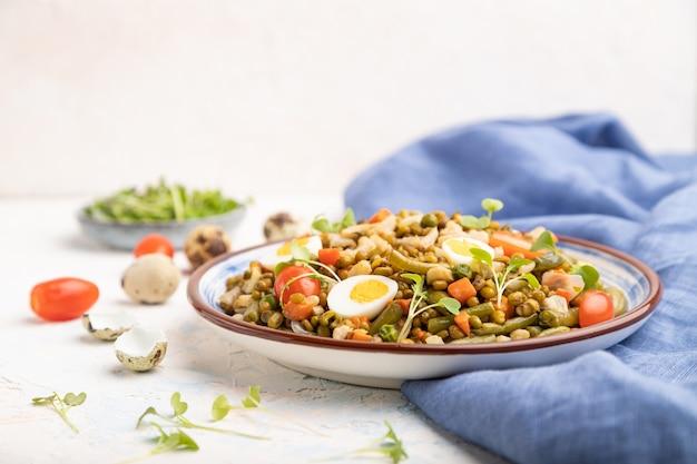 Mungboonpap met kwarteleitjes, tomaten en microgreen spruitjes op een witte betonnen tafel en blauw textiel. zijaanzicht, kopieer ruimte.