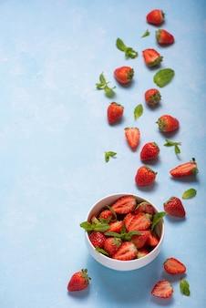 Munt en rijpe aardbeien in een witte kom op een blauwe achtergrond