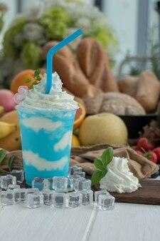 Munt en yoghurt smoothies op een houten plaat met ijsblokjes en fruit als achtergrond