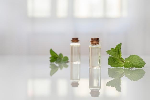Munt etherische olie in kleine glazen flesjes op tafel.