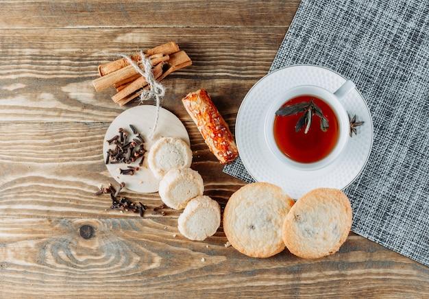 Muntachtige thee met kaneelstokjes, koekjes, kruidnagel in een kopje op houten oppervlak
