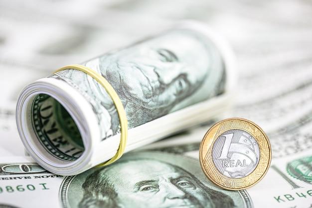 Munteenheid van een braziliaanse real op bankbiljetten van 100 amerikaanse dollars. concept hoge dollar tegen de devaluatie van de munteenheid van brazilië