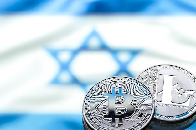 Munten bitcoin en litecoin, tegen de achtergrond van de israëlische vlag, concept van virtueel geld, close-up. conceptueel beeld