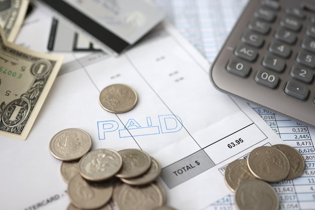 Munten en dollarbiljetten die op documenten liggen met getallen in de buurt van de economische crisis van de rekenmachineclose-up