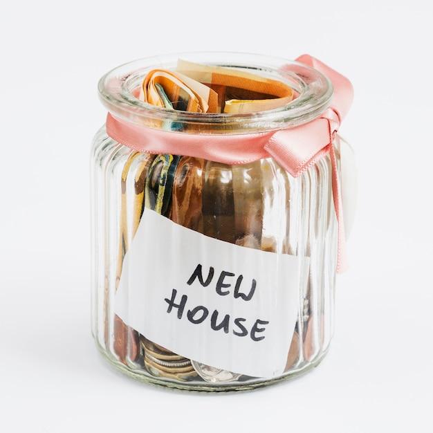 Munten en eurobiljetten in de glazen pot versierd met roze lint verzameld voor nieuw huis