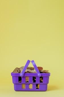 Munten in een winkelmandje. van financiën en geld. een investering in een nieuw project. rijkdom en armoede. winkelen in de winkel. geel. copyspace.
