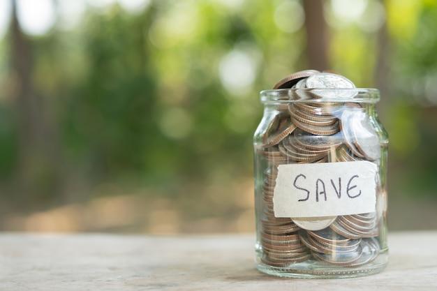 Munten in glazen pot voor geldbesparend financieel concept