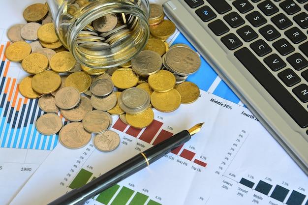 Munten morsen uit pot op de zakelijke aandelengrafieken - business concept