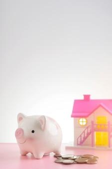 Munten rond spaarvarken op roze lijst met zoete huisachtergrond. sparen om een huis of een huisbesparingsconcept te kopen