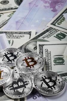 Munten van bitcoin op de achtergrond van bankbiljetten van dollars
