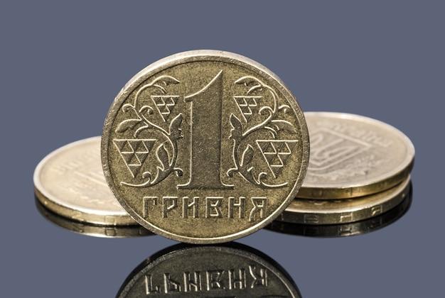Munten van één oekraïense hryvnia op een grijze achtergrond
