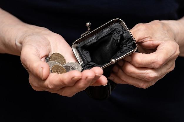 Munten van tien roebel worden in de handen van een gepensioneerde gegoten, het concept van armoede
