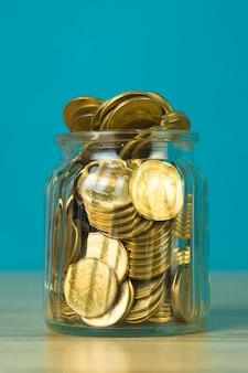 Muntgeld in de glazen pot op tafel met groene scène