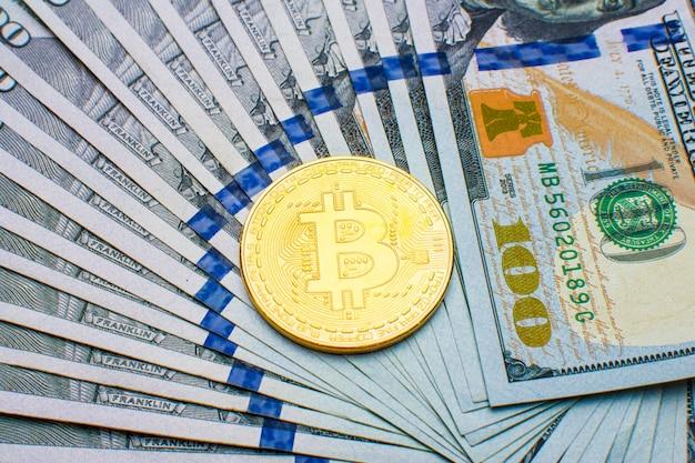 Muntstukken bitcoin btc op achtergrond van bankbiljetten honderd dollars