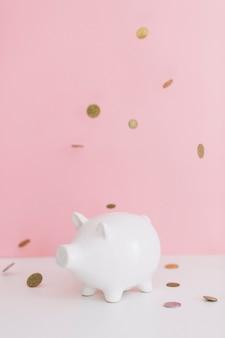 Muntstukken die over witte piggybank tegen roze achtergrond vallen