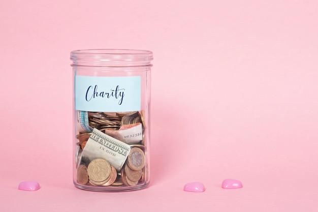 Muntstukken en bankbiljetten in de pot van het glasgeld, financiële schenkingen, liefdadigheidsconcept