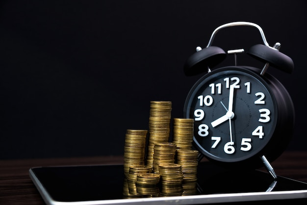 Muntstukkenstapels en wekker met tabletcomputer en financiële grafiek, bedrijfs planningsvisie en het concept van de financiënanalyse