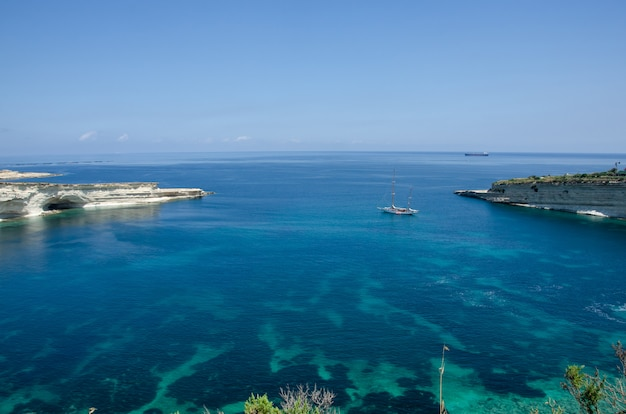 Munxar pad in de buurt van marsaskala, malta. witte rotsen met blauw water in malta dichtbij marsaxlokk, heilige peter pool.