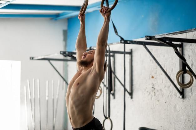 Muscle-up oefening atletische man intensieve training op sportschool op gymnastische ringen