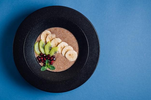 Mush. veganistisch. in gehydrateerde, plantaardige melk, banaan, honing, kiwi, granaatappel. op plaat geïsoleerd op blauwe achtergrond, close-up, bovenaanzicht