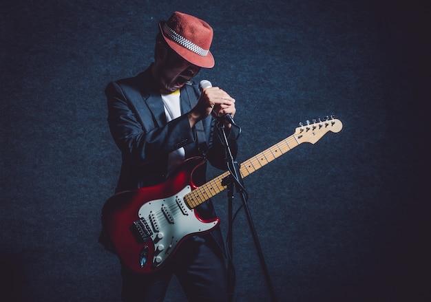 Musicus die de gitaar met hand speelt die de microfoon en het zingen houdt