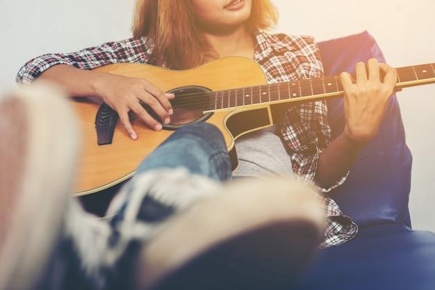 Musicus gitaar spelen in een coach
