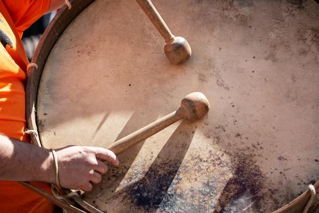 Musicushanden met trommelstokken die een bastrommel spelen tijdens een openluchtfestival