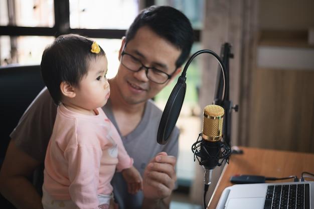 Musicusmens en zijn dochter die muziek opnemen in de studio van het muziekhuis
