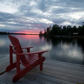 Muskoka stoel op het dok bij zonsondergang in lake of the woods, ontario