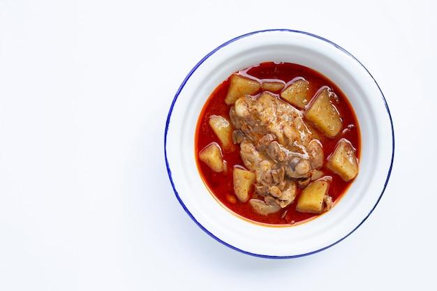 Mussamankerrie met kip en aardappel op witte achtergrond.