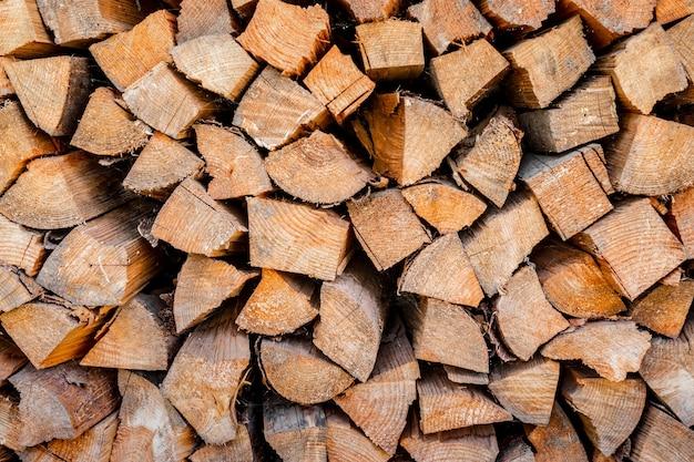 Muur brandhout, achtergrond van droge gehakte brandhout logs in een stapel. brandhout textuur. stapel droge gehakte houten logboeken. natuurlijke houten achtergrond met hout.