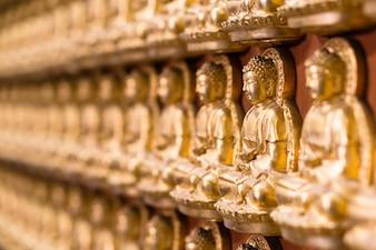 Muur in tempel gemaakt door duizend kleine gouden Boeddha