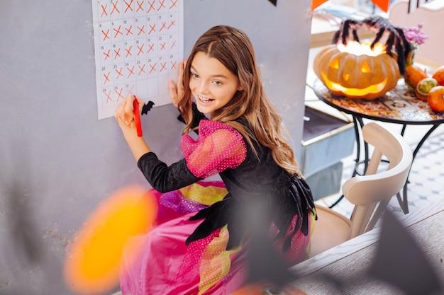 Muur kalender. grappig modieus meisje dat roze en zwarte halloween-kleding draagt die zich dichtbij haar muurkalender bevindt