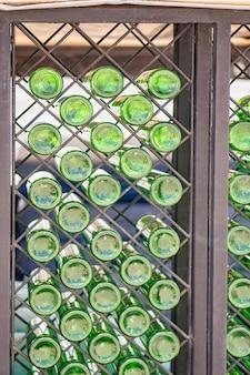 Muur met groene glazen flessen op de plank. interieur decoratie