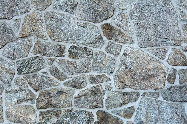 Muur met het leggen van natuursteen van verschillende texturen.