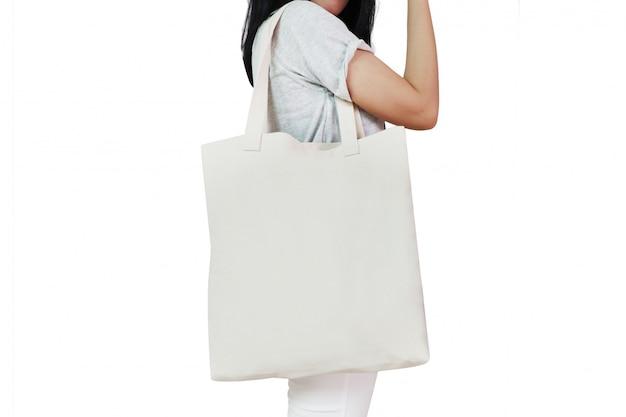 Muur van aziatische vrouw houden canvas tote tas met lege ruimte voor ontwerp
