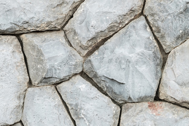 Muur van de close-up de oude steen op de achtergrond van de tuintextuur