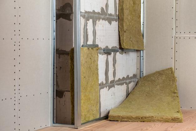 Muur van een kamer in renovatie met minerale steenwol isolatie en metalen frame voorbereid voor gipsplaten.