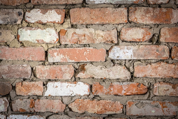 Muur van een oud bakstenen gebouw met gepeld gips en geschilderde textuurachtergrond