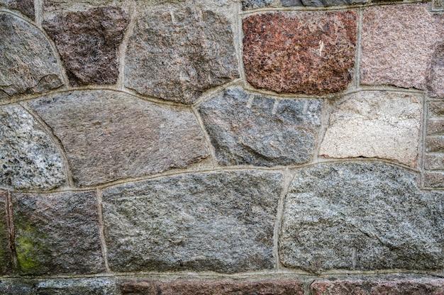 Muur van graniet geweven stenen samen gecementeerd