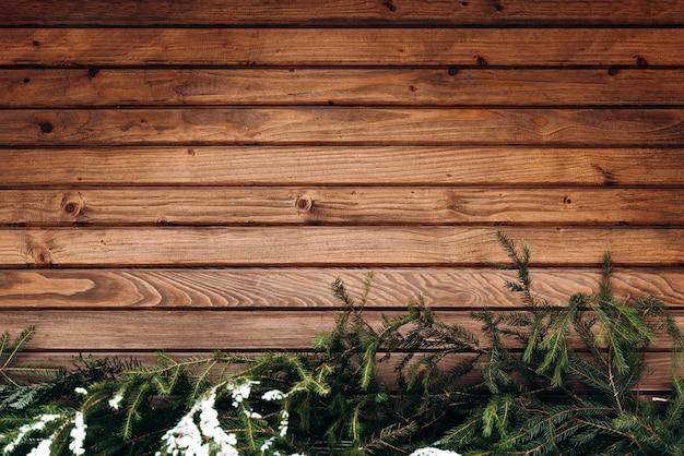 Muur van houten hek. winter houten plank achtergrond, bruine horizontale planken, houtstructuur, hek. spar brunches aan de onderkant. stock foto