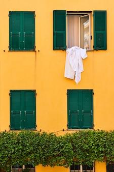 Muur van huis met ramen met luiken in de wijk boccadasse in genua (genua), italië - architectonisch detail