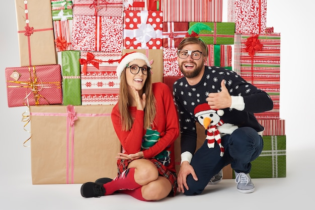 Muur van kerstcadeautjes en vrolijk paar
