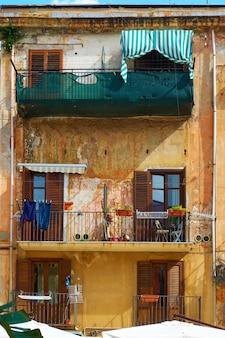 Muur van oud gebouw met balkons in palermo, sicilië, italy
