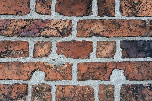 Muur van oude gebarsten rode baksteen met zwarte insluitsels.