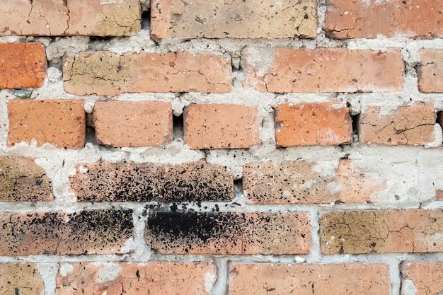 Muur van oude oranjerode gebarsten baksteen met een dikke laag cement ertussen. sommige stenen hebben een zwarte vlek