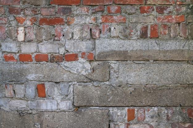 Muur van rode baksteen en grijze betonnen platen