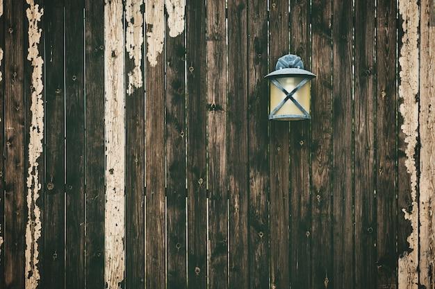 Muur van verweerde houten verticale planken met een oude lamp erop